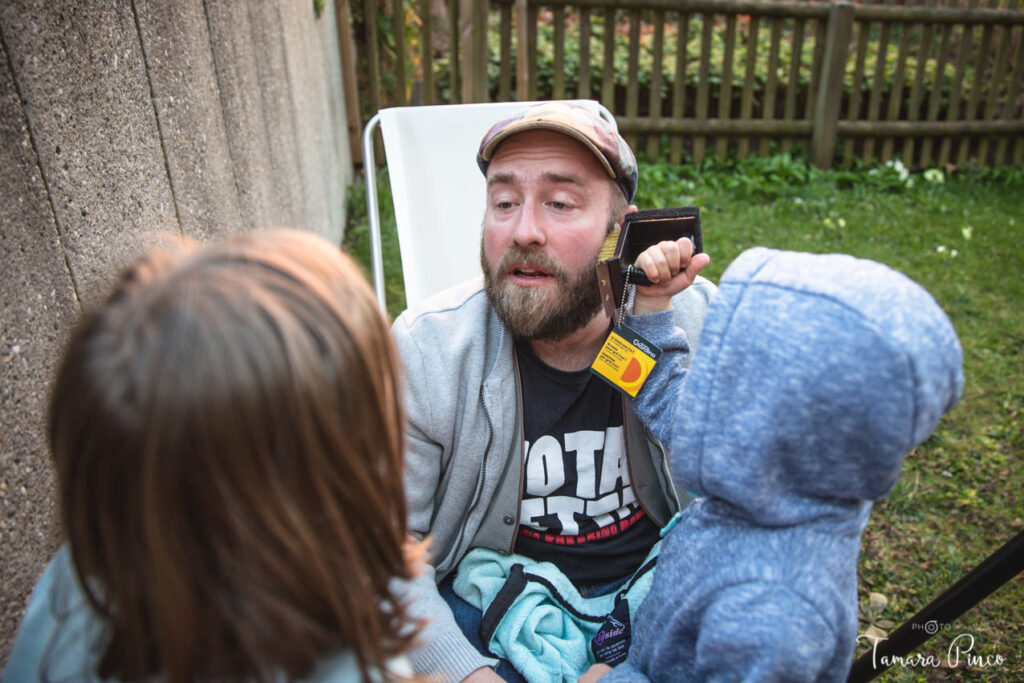 A father is talking to her daughters, while one of them comb his beard with a metal brush